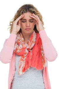 Blonde girl touching her temples because of a headache on white background